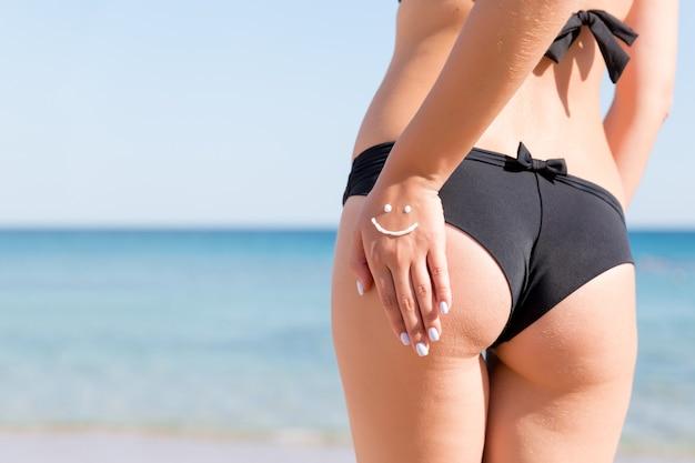 Ładna kobieta zrobiła z kremu przeciwsłonecznego na swoim tyłku na plaży.