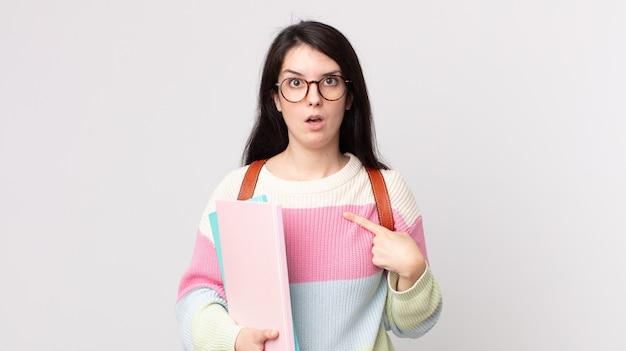 Ładna kobieta, zszokowana i zaskoczona, z szeroko otwartymi ustami, wskazując na siebie. koncepcja studenta uniwersytetu