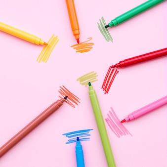 Ładna kompozycja z kolorowymi markerami na różowym tle