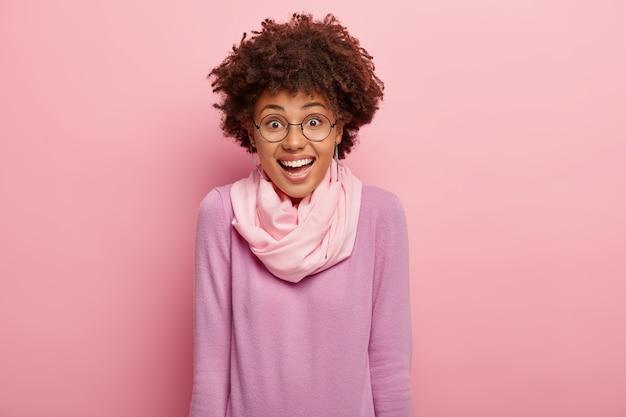 Ładna kręcona kobieta wyraża radość, cieszy się zabawną chwilą, śmieje się z czegoś, uśmiecha się pozytywnie, nosi okrągłe okulary