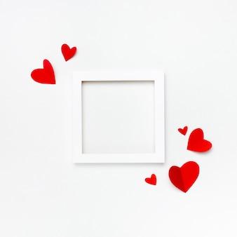 Ładna kwadratowa biała ramka z copyspace dla tekstu na białym tle ozdobiona ręcznie robionymi papierowymi sercami