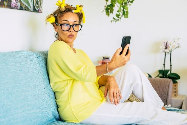 Ładna, ładna kaukaska kobieta w domu robi wideokonferencję lub szalenie miła ekspresja przez telefon, aby zrobić zdjęcie, aby udostępnić online