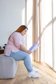 Ładna ładna kobieta siedzi przy oknie podczas czytania magazynu kosmetycznego