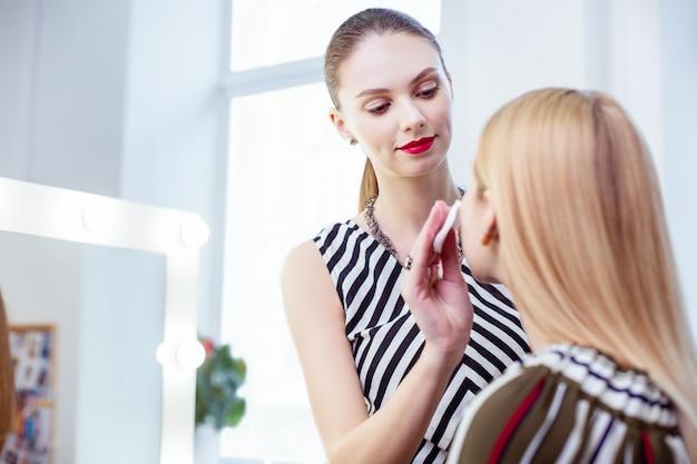 Ładna, ładna kobieta używająca wacika podczas oczyszczania skóry swoich klientów