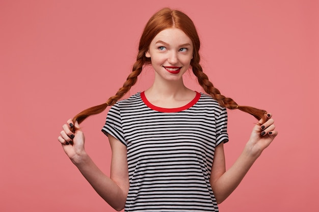 Ładna ładna rudowłosa dziewczyna z czerwonymi ustami trzymająca dwa warkocze w rękach ubrana w t-shirt w paski, flirtująca figlarnie patrząc na lewy górny róg kreśląc przygodę na białym tle