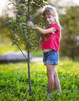 Ładna ładna uśmiechnięta dziewczynka z szarymi oczami i długimi blond włosami w letnim ubraniu, trzymając młode zielone drzewko na niewyraźne słoneczny park lub ogród