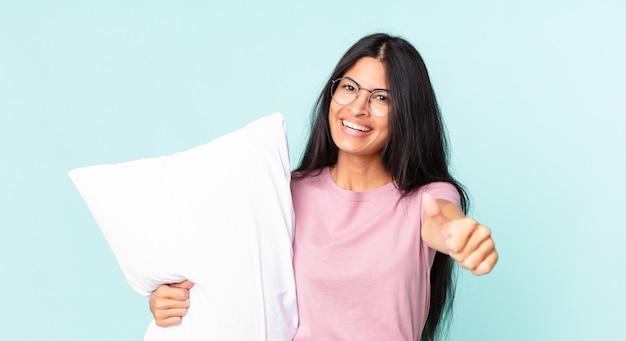 Ładna latynoska kobieta czuje się dumna, uśmiecha się pozytywnie z kciukami do góry i ma na sobie piżamę z poduszką