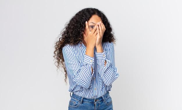 Ładna latynoska kobieta czuje się przestraszona lub zawstydzona, zerka lub szpieguje z oczami na wpół zakrytymi rękami
