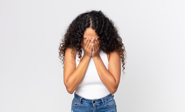 Ładna latynoska kobieta czuje się smutna, sfrustrowana, zdenerwowana i przygnębiona, zakrywa twarz obiema rękami, płacze