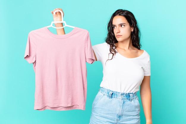 Ładna latynoska kobieta czuje się smutna, zdenerwowana lub zła i patrzy w bok wybierając ubranie