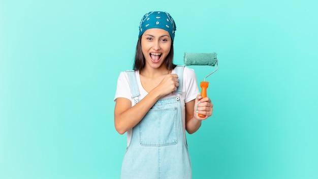 Ładna latynoska kobieta czuje się szczęśliwa i staje przed wyzwaniem lub świętuje. koncepcja malowania domu