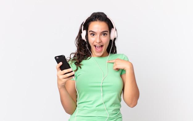 Ładna latynoska kobieta czuje się szczęśliwa i wskazuje na siebie z podekscytowaniem ze słuchawkami i smartfonem