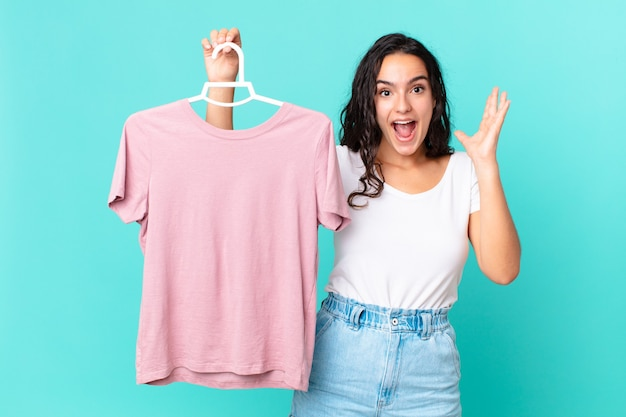 Ładna latynoska kobieta czuje się szczęśliwa i zaskoczona czymś niewiarygodnym wybierając ubranie