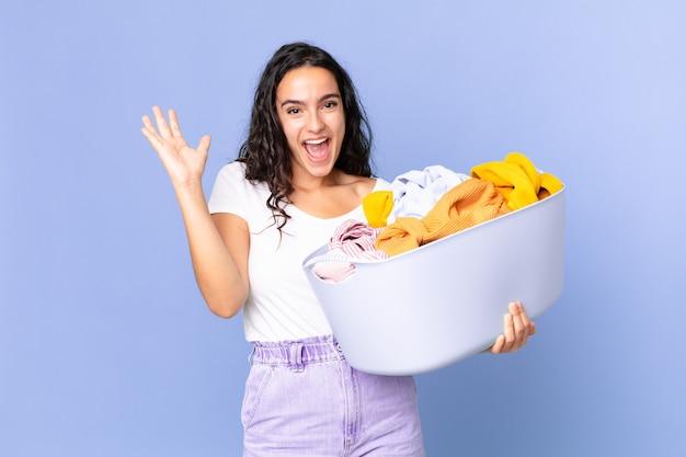 Ładna latynoska kobieta czuje się szczęśliwa i zdumiona czymś niewiarygodnym i trzyma kosz na pranie