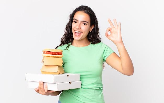 Ładna latynoska kobieta czuje się szczęśliwa, okazując aprobatę dobrym gestem i trzymając pudełka z fast foodami na wynos