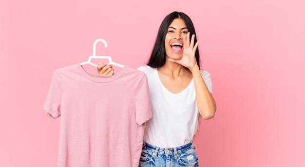 Ładna latynoska kobieta czuje się szczęśliwa, wydając wielki okrzyk z rękami przy ustach i trzymając wybrany materiał
