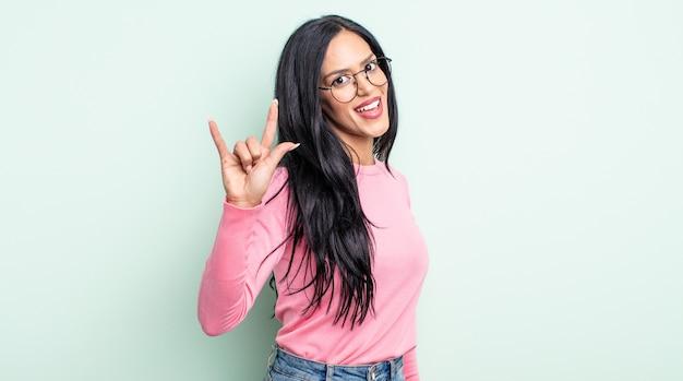 Ładna latynoska kobieta czuje się szczęśliwa, zabawna, pewna siebie, pozytywna i zbuntowana, wykonując ręką rockowy lub heavy metalowy znak