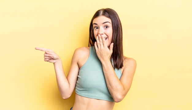 Ładna latynoska kobieta czuje się szczęśliwa, zszokowana i zaskoczona, zakrywa usta dłonią i wskazuje boczną przestrzeń do kopiowania