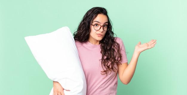 Ładna latynoska kobieta czuje się zakłopotana i zdezorientowana, wątpi i nosi piżamę z poduszką