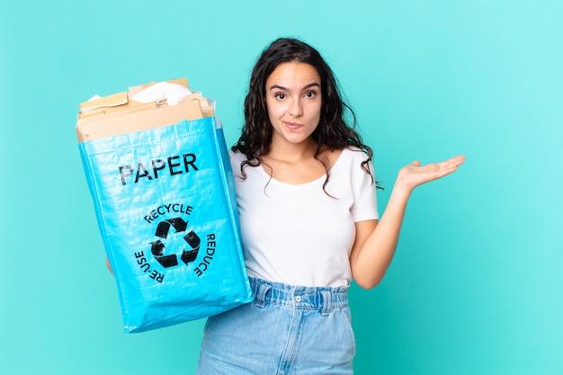 Ładna latynoska kobieta czuje się zakłopotana i zdezorientowana, wątpi i trzyma papierową torbę z recyklingu