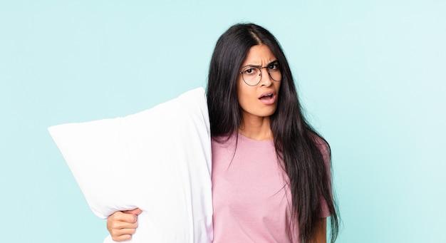 Ładna latynoska kobieta czuje się zdezorientowana i zdezorientowana i ma na sobie piżamę z poduszką