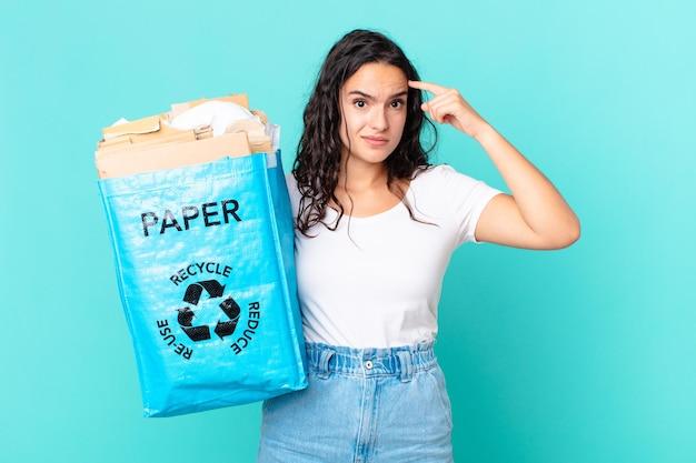 Ładna latynoska kobieta czuje się zdezorientowana i zdezorientowana, pokazując, że jesteś szalony i trzymasz papierową torbę z recyklingu