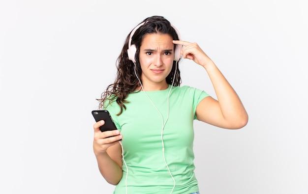 Ładna latynoska kobieta czuje się zdezorientowana i zdezorientowana, pokazując, że jesteś szalony ze słuchawkami i smartfonem