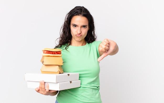 Ładna latynoska kobieta czuje się ze złością, pokazuje kciuki w dół i trzyma pudełka z fast foodami na wynos