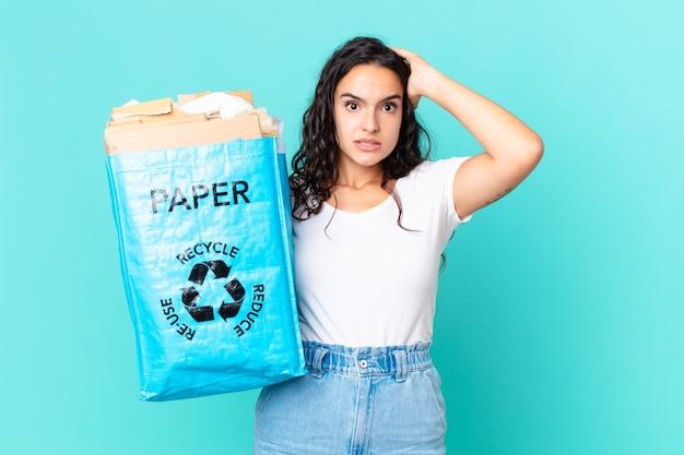 Ładna latynoska kobieta czuje się zestresowana, niespokojna lub przestraszona, z rękami na głowie i trzymająca papierową torbę z recyklingu