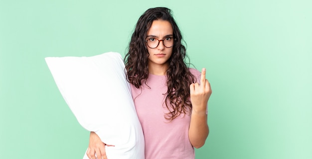 Ładna latynoska kobieta czuje się zła, zirytowana, buntownicza i agresywna i ma na sobie piżamę z poduszką