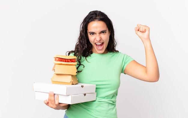 Ładna latynoska kobieta krzycząca agresywnie z gniewnym wyrazem twarzy i trzymająca na wynos pudełka z fast foodami