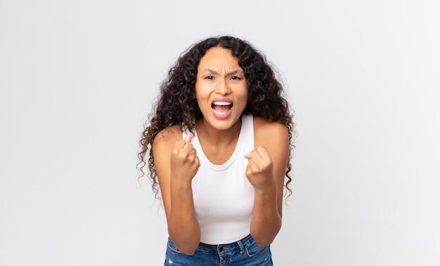Ładna latynoska kobieta krzycząca agresywnie ze zirytowanym, sfrustrowanym, gniewnym spojrzeniem i zaciśniętymi pięściami, czując się wściekła