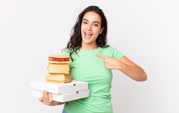 Ładna latynoska kobieta, która wygląda na podekscytowaną i zaskoczoną, wskazując na bok i trzymając na wynos pudełka z fast foodami