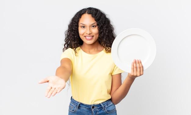 Ładna latynoska kobieta trzyma puste, czyste naczynie
