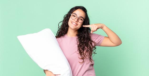 Ładna latynoska kobieta uśmiecha się pewnie wskazując na swój szeroki uśmiech i ma na sobie piżamę z poduszką