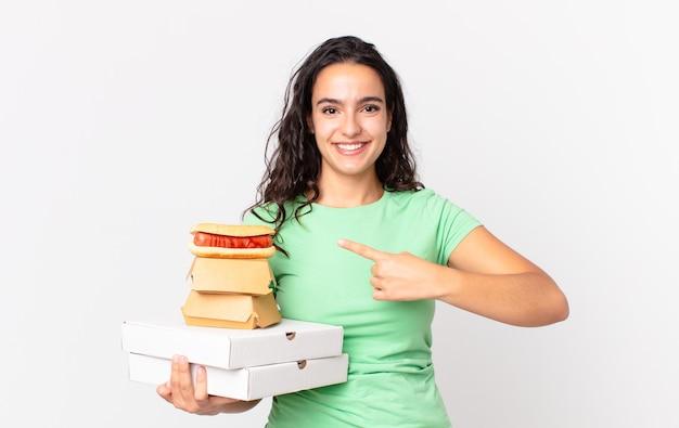 Ładna latynoska kobieta uśmiecha się radośnie, czuje się szczęśliwa i wskazuje na bok i trzyma na wynos pudełka z fast foodami