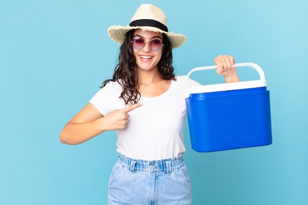 Ładna latynoska kobieta uśmiecha się radośnie, czuje się szczęśliwa i wskazuje na bok trzymając przenośną lodówkę