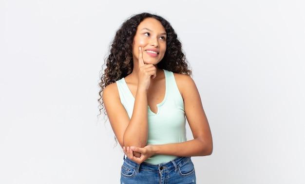 Ładna latynoska kobieta uśmiecha się radośnie i marzy lub wątpi, patrząc w bok