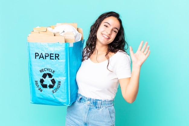 Ładna latynoska kobieta uśmiecha się radośnie, macha ręką, wita cię i wita i trzyma papierową torbę z recyklingu