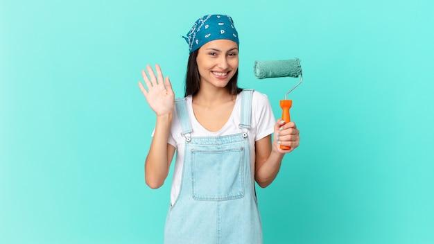 Ładna latynoska kobieta uśmiecha się radośnie, macha ręką, wita cię i wita. koncepcja malowania domu