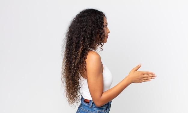 Ładna latynoska kobieta uśmiecha się, wita cię i oferuje uścisk dłoni, aby zamknąć udaną transakcję, koncepcja współpracy