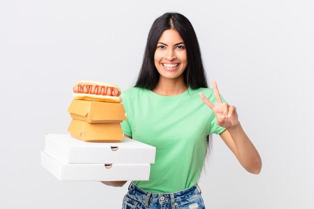 Ładna latynoska kobieta uśmiechająca się i wyglądająca na szczęśliwą, gestykulującą zwycięstwo lub pokój i trzymająca na wynos pudełka z fast foodami