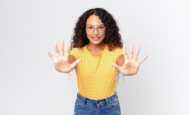 Ładna latynoska kobieta uśmiechająca się i wyglądająca przyjaźnie, pokazująca cyfrę dziesięć lub dziesiątą z ręką do przodu, odliczając w dół