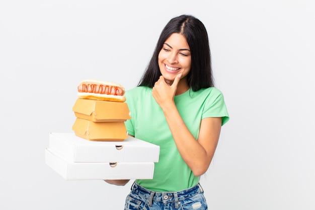 Ładna latynoska kobieta uśmiechająca się ze szczęśliwym, pewnym siebie wyrazem twarzy z ręką na brodzie i trzymająca pudełka z fast foodami na wynos