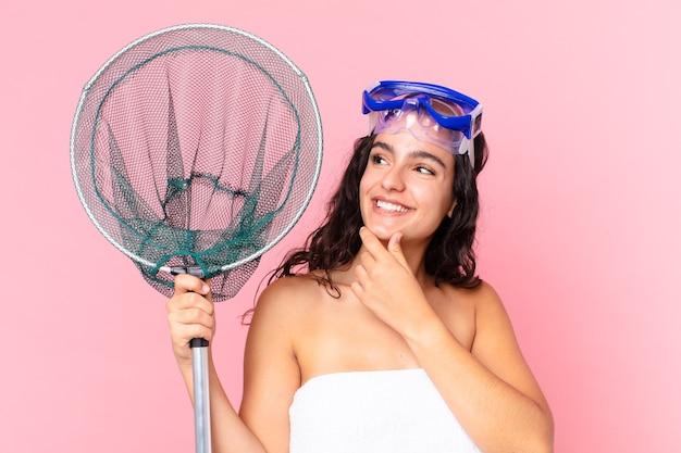 Ładna latynoska kobieta uśmiechająca się ze szczęśliwym, pewnym siebie wyrazem twarzy z ręką na brodzie z goglami i siecią rybacką