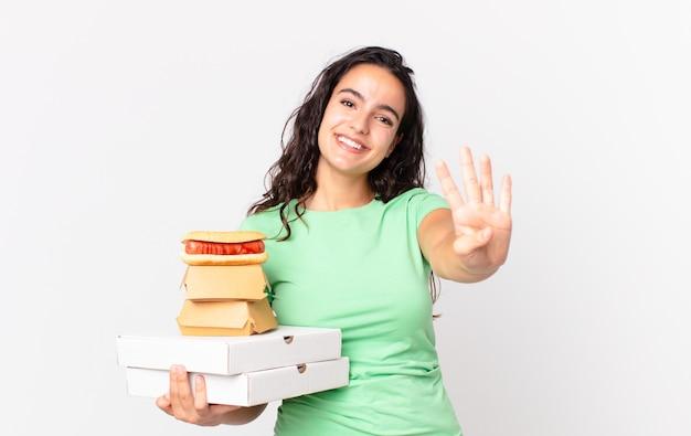Ładna latynoska kobieta uśmiechnięta i wyglądająca przyjaźnie, pokazująca numer cztery i trzymająca pudełka z fast foodami na wynos