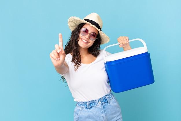 Ładna latynoska kobieta uśmiechnięta i wyglądająca przyjaźnie, pokazująca numer jeden, trzymająca przenośną lodówkę