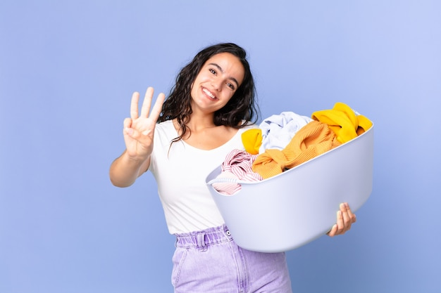 Ładna latynoska kobieta uśmiechnięta i wyglądająca przyjaźnie, pokazująca numer trzy i trzymająca kosz na pranie
