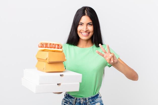Ładna latynoska kobieta uśmiechnięta i wyglądająca przyjaźnie, pokazująca numer trzy i trzymająca pudełka z fast foodami na wynos