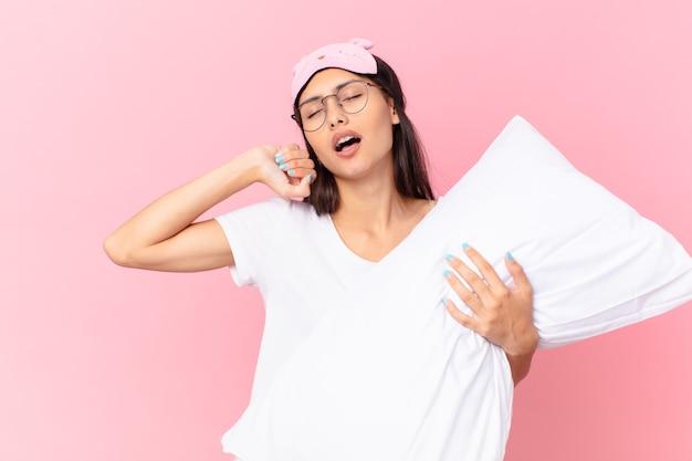 Ładna latynoska kobieta w piżamie i trzymająca poduszkę